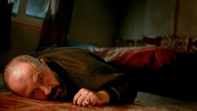 Ein Mann liegt Holzboden.
