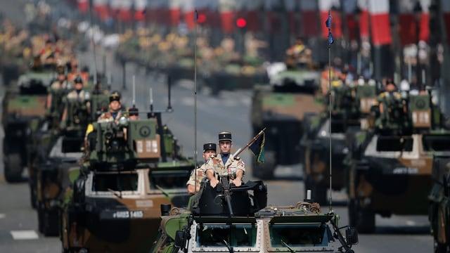 Französische Armeeangehörige werden im Panzer durch Paris gefahren.