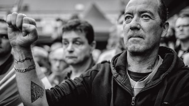 Ein Mann bei einer Rede von Le Pen, mit gereckter Faust.