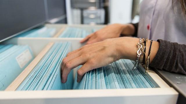 Eine Frau sucht in einem Hängeregister nach einem Patientendossier