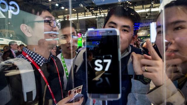 Symbolbild: Junge Asiaten stehen gebannt um ein Smartphone Galaxy 7 in einem Schaukasten herum.