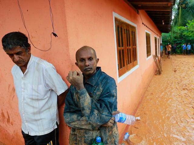 Zwei Bewohner neben nehen einem Haus