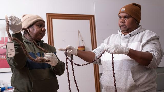 Zwei Frauen halten traditionelle Objekte der Aboriginies in der Hand.