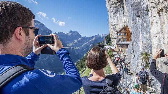 Wandertouristen fotografieren das spektakulär gelegene Restaurant Aescher im Alpstein.