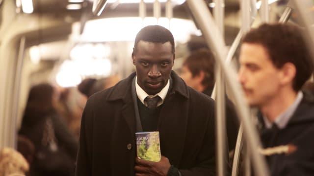 Ein schwarzer Manner steht in der U-Bahn. Er scheint verloren.