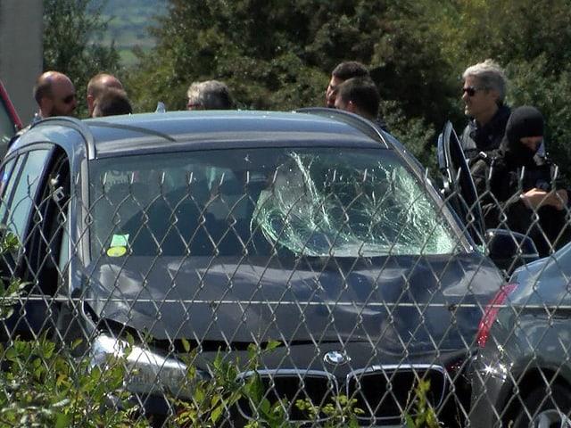 Ein schwarzer BMW mit kaputter Scheibe. Mehrere Sicherheitskräfte stehen daneben.