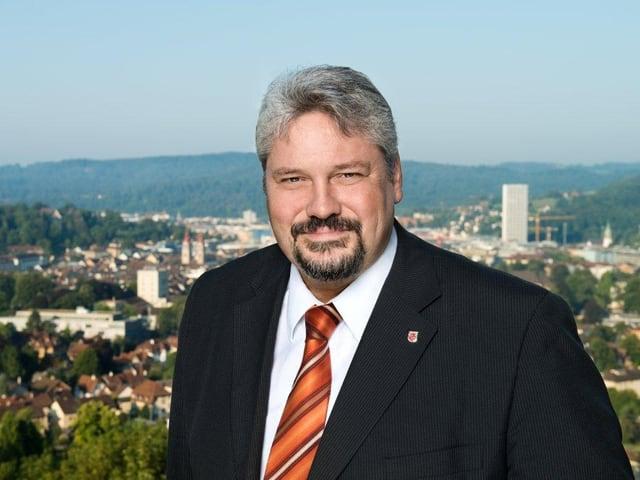 Ein Mann, breit gebaut, mit grauen Haaren und Kinnbart vor der Stadt Winterthur