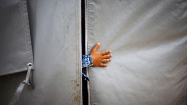 Eine Hand ragt aus einem Zelt.
