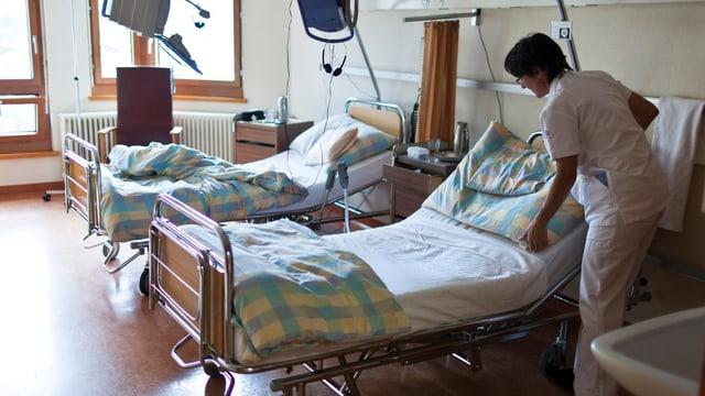 Eine Krankenschwester macht das Bett in einem Krankenzimmer.