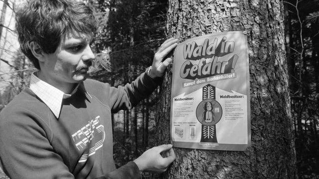 Ein Mann steht neben einem Plakat, dass an einem Baum angebracht ist.