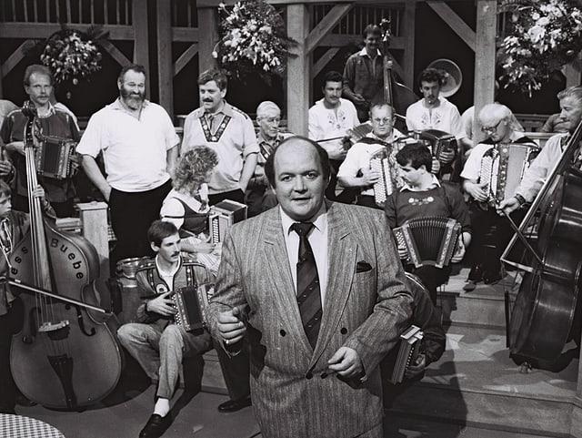 Ein Moderator vor einer Volksmusik-Formation.