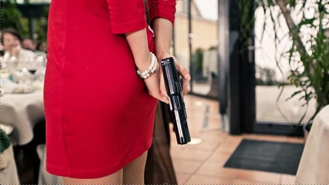 Eine Frau in einem Restaurant hält eine Pistole in der Hand.