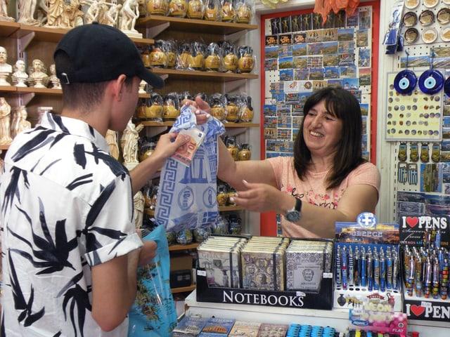 Vassiliki übergibt einem Kunden eine Tüte.