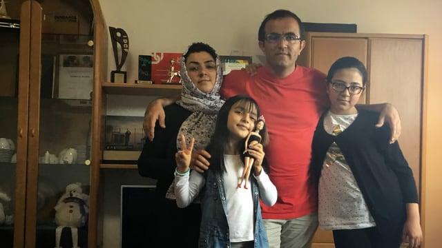 Mutter, Vater und zwei Kinder posieren vor der Kamera.