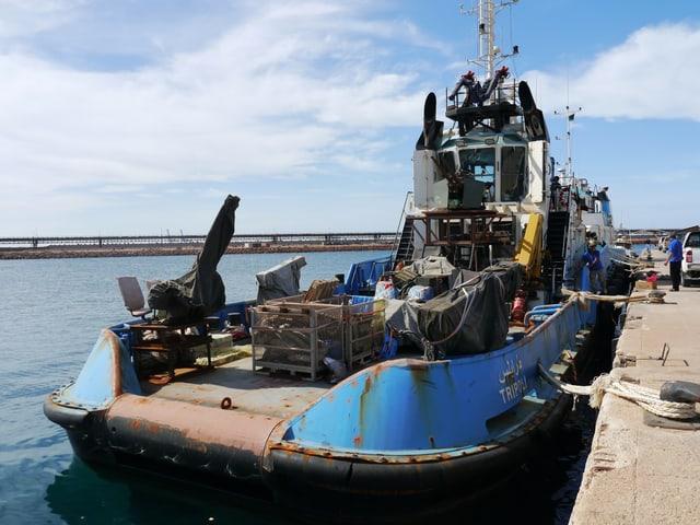 Ein rostiges Boot liegt vertäut in einem Hafen.