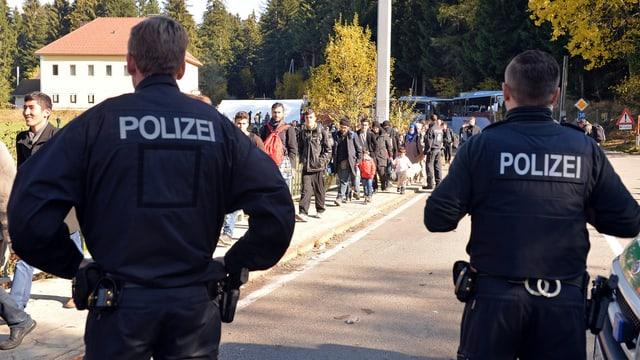 Zwei deutsche Polizisten beobachten eine Gruppe von Flüchtlingen.