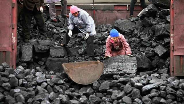 Arbeiter laden Kohle von einem Laster.