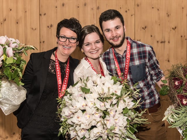 Die drei posieren mit Medaillen und Blumensträussen für den Fotografen.