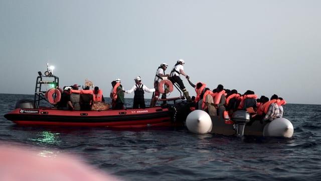 Ein Rettungsboot hilft Flüchtlingen um von ihrem Schlauchboot auf ein grösseres Gefährt zu wechseln.