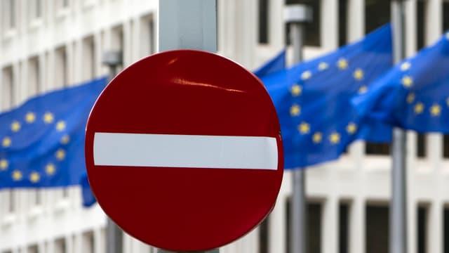 Ein Verkehrsschild mit dem Verbotszeichen steht vor der europäischen Flagge.