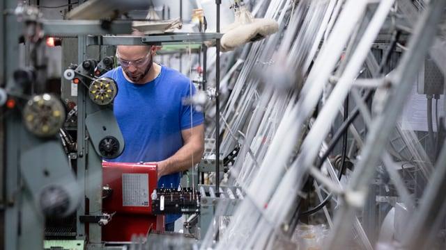 Um che lavura en ina fabrica da textil en ils Stadis Unids da l'America.