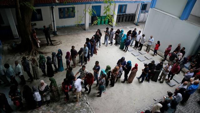 Wähler stehen Schlange bei einem Wahllokal