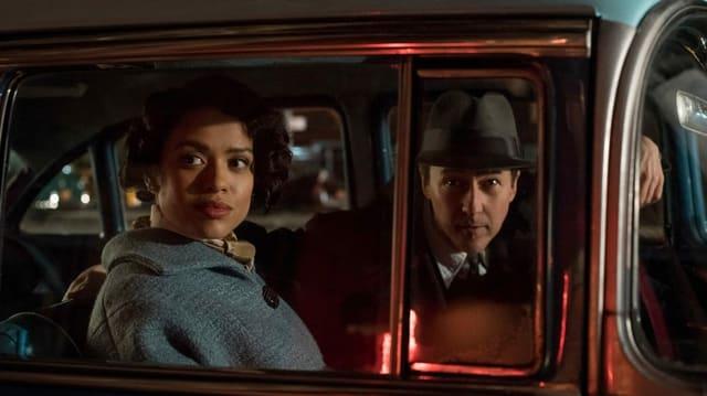 Eine Frau und ein Mann sitzen in einem Fünfzigerjahre-Auto.