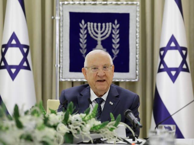 Älterer Herr (Reuven Rivlin) spricht flankiert von israelischen Flaggen