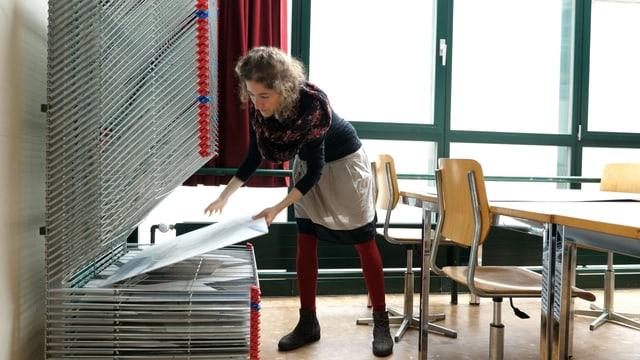 Eine Fraumacht sich in einem Schulzimmer an grossen zeichnungsbögen zu schaffen.