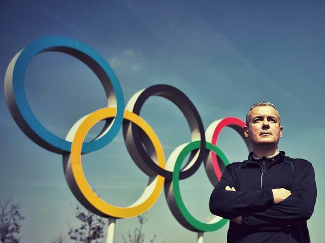 Der Schriftsteller Ilija Trojanow steht mit verschränkten Armen neben den olympischen Ringen.