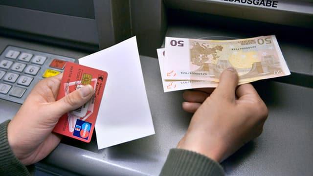 Ein Kunde nimmt Euro aus dem Bancomat