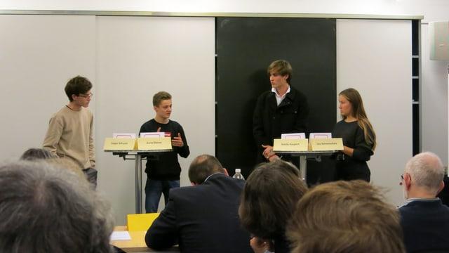 Vier Jugendliche stehen in einem Schulzimmer an Stehtischen, im Vordergrund Köpfe von Publikum und Jury.