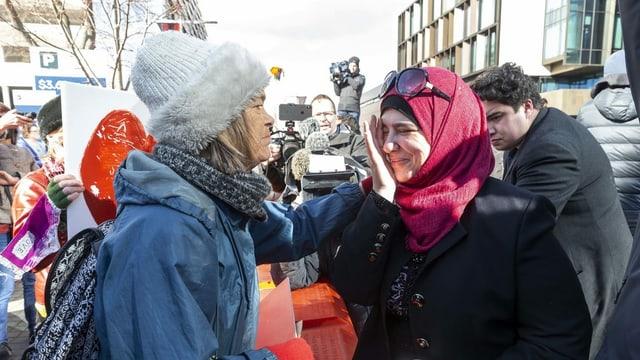 Frau tröstet andere Frau, die ein Kopftuch trägt.