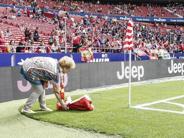 Atletico-Fan Margarita Luengo platziert ein Blumenbouquet an der Eckfahne.