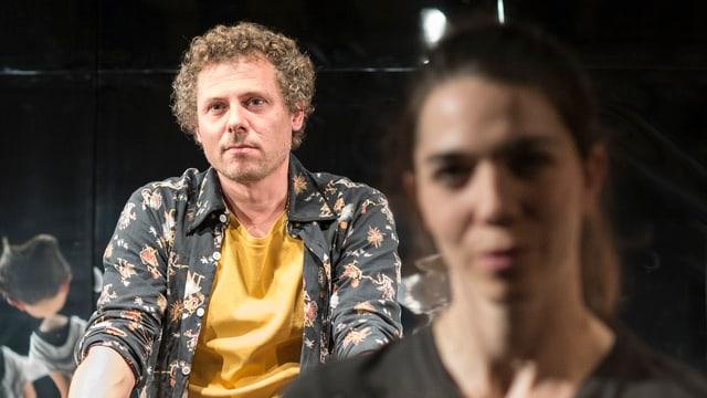 LInks sitzt Löliger auf einem Fahrrad, rechts zu sehen in der Unschärfe Schauspielerin Judith Cuénod.