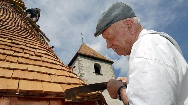 Ein älterer Mann arbeitet an einem Hausdach