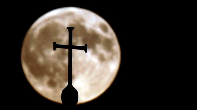 Ein Kreuz einer Kirche vor dem Vollmond.