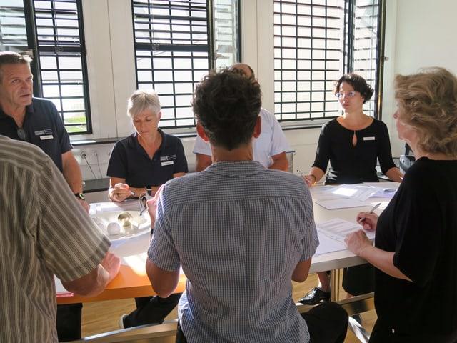 Eine Gruppe Erwachsener steht um einen Tisch, darauf liegen Papiere.