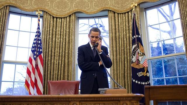 Obama in seinem Büro, er telefoniert.