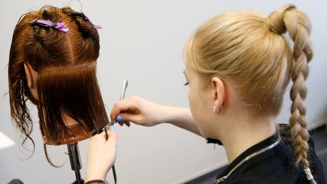Eine Coiffeurlernende schneidet die Haare eines Modellkopfes.