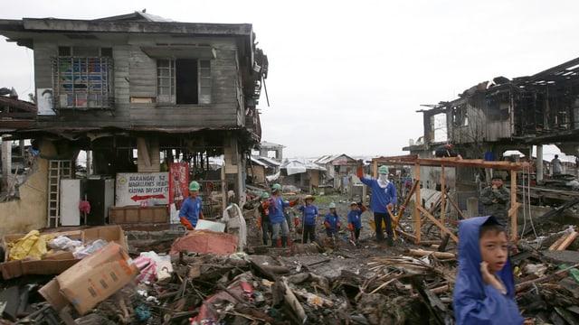 Kinder bauen aus Brettern eine neue Hütte in der verwüsteten Stadt Tacloban auf den Philippinen.