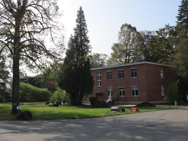 Bachsteinhaus auf einer Wiese.