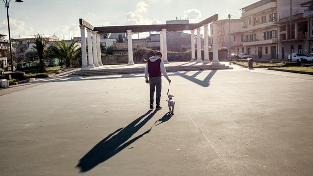 Ein Junge führt seinen Hund spazieren, im Hintergrund eine Art Torbogen.