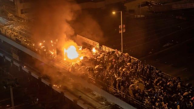 Demonstranten zündeten ausserhalb der Polytechnischen Universität ein Polizeiauto an, auf der Brücke kam es zu Zusammenstössen.
