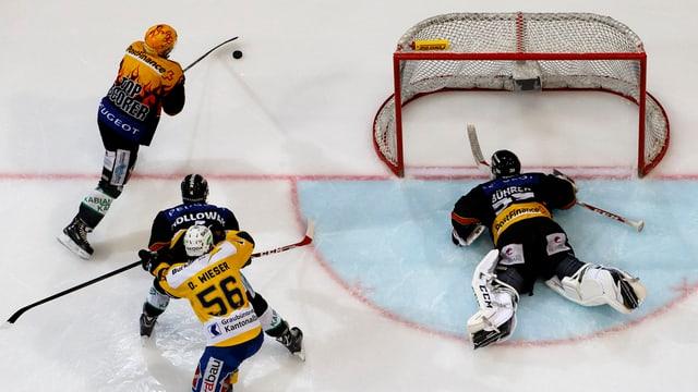 4 giugaders da hockey sin glatsch avant il gol.