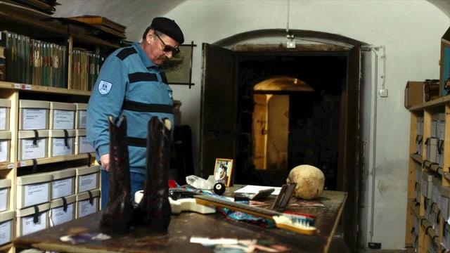 Ein Mann mit Beret steht im Keller und blickt auf einen Schreibtisch auf dem viele Erinnerungsstücke und Bilder stehen.