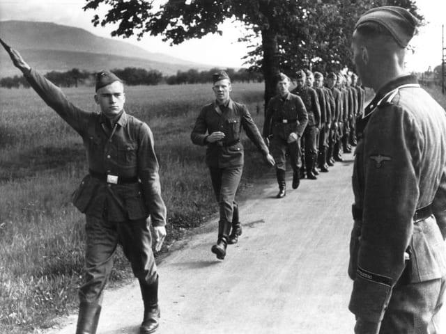 Soldaten marschieren hintereinander auf einem Feldweg. Der Forderste hebt den Arm zum Hitler-Gruss.
