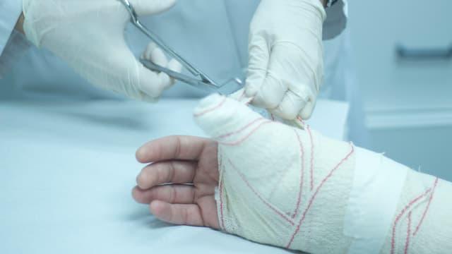Ein Arzt bindet eine Hand ein