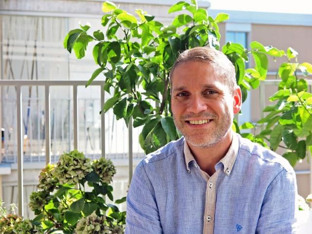 Porträtbild eines 40-jährigen Mannes vor einer grünen Pflanze.