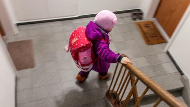 Ein Kind steigt ein Treppenhaus hinunter.